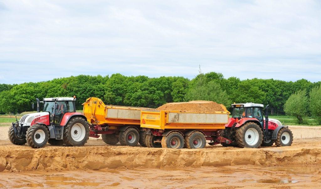 Tractor met dumper en haakarm